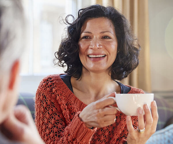 hispanic woman having coffee in a groupr ecovering from alzheimer's and dementia